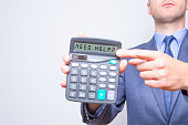 Young businessman pointing on calculator.Need Help? Sign. Taxes business concept