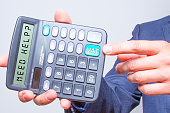 Young businessman pointing on calculator.Need Help? Vat Sign. Taxes business concept