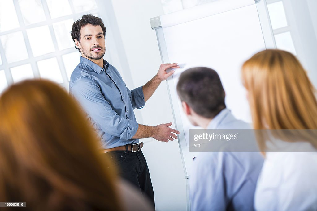Young Businessman Presenting His Ideas on Flip Chart to Colleagues : Stock Photo