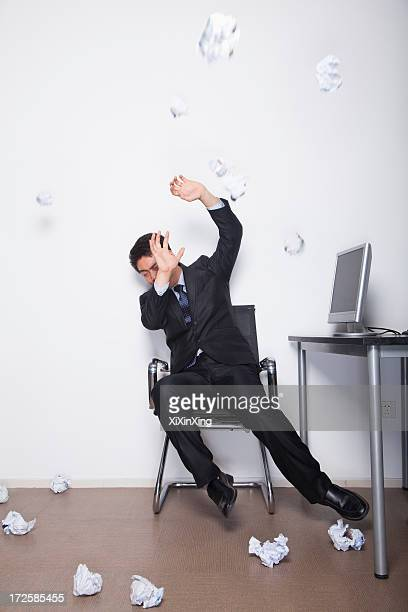Young Businessman protecting himself from being hit by crumpled up pieces of paper