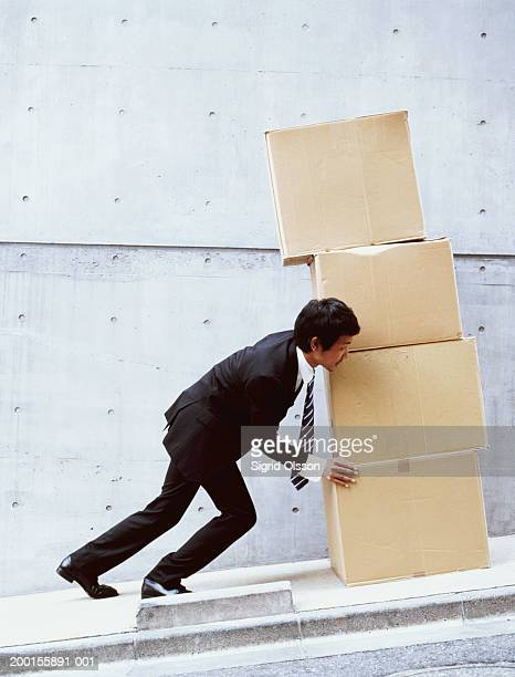 Young businessman pushing stack of boxes up hill, side view