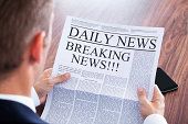 Young Businessman Reading Breaking News On Newspaper