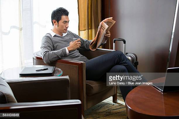 Young businessman reading newspaper in hotel room