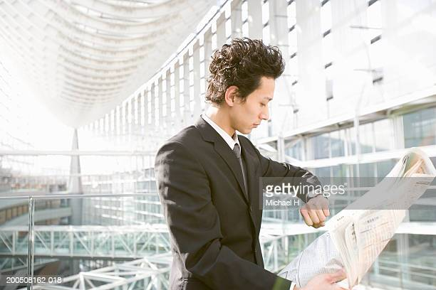 Young businessman reading newspaper, looking at watch, side view