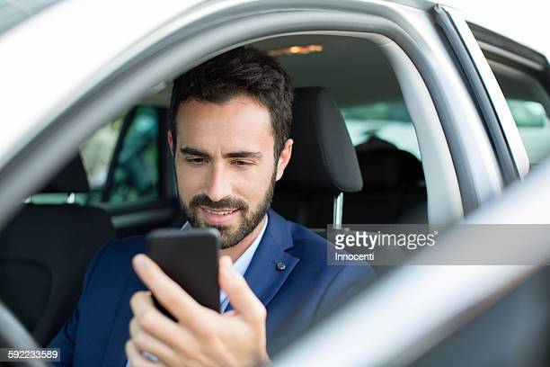 Young businessman reading smartphone texts in car