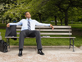 Young businessman relaxing on park bench