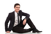 Young businessman sitting on the floor. Full length studio shot isolated on white.