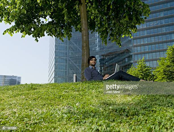 young businessman relaxing under tree