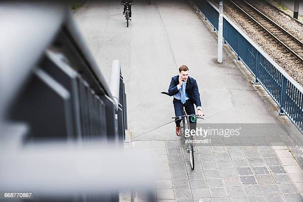 Young businessman riding bike while talking on the phone