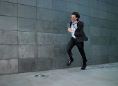 Young businessman running against wind