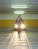 Young businessman running from car in garage (blurred motion)
