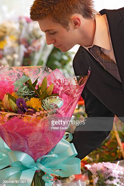 Young businessman selecting bouquet of flowers, side view, close-up