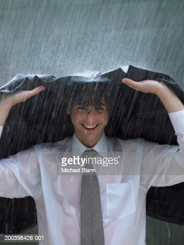 Young businessman sheltering under jacket, smiling, portrait, close-up