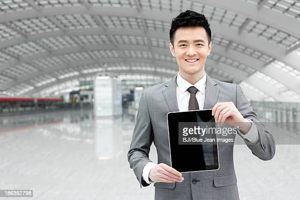 Young businessman showing digital tablet  at the airport