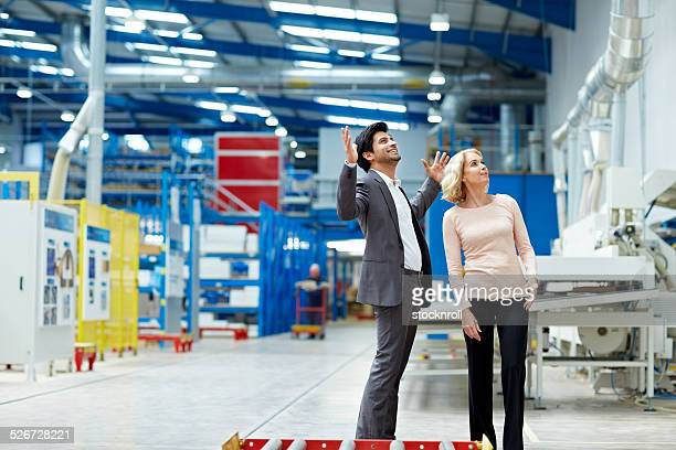 Young businessman showing his factory to a female visitor