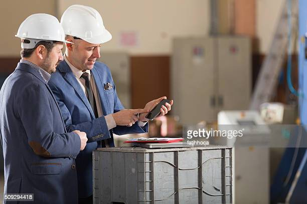 Young businessman showing mobile phone