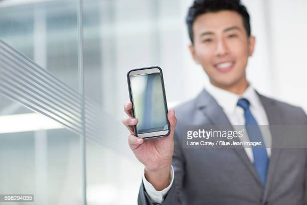 Young businessman showing smart phone