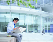 Young Businessman Sits Reading Newspaper Outside Glass Office Block