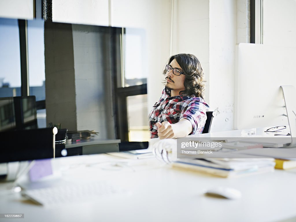 Young businessman sitting at desk in office : Stock Photo