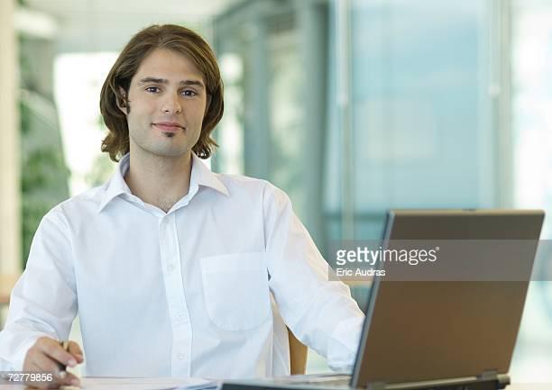 Young businessman sitting at desk, smiling at camera