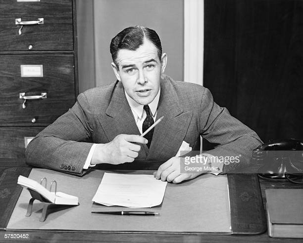 Young businessman sitting at small desk, holding pencil, (B&W)