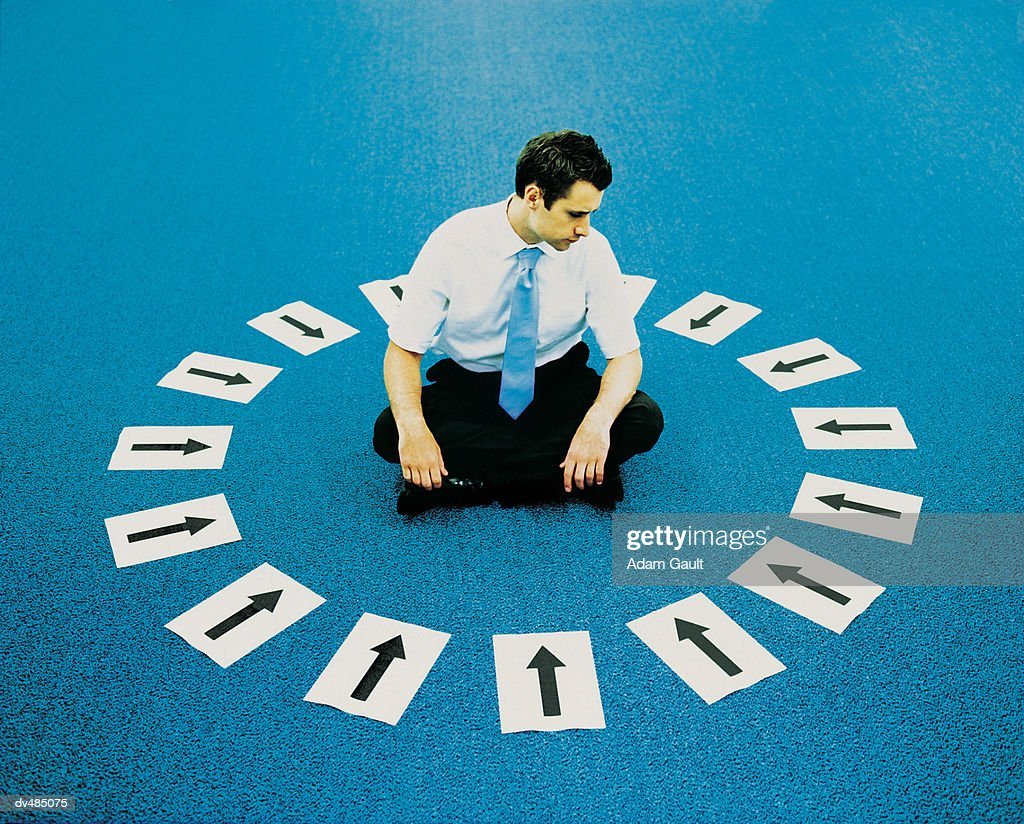 Young Businessman Sitting Cross Legged on the Carpet Inside a Circle of Arrow Signs Pointing Inwards : Stock Photo