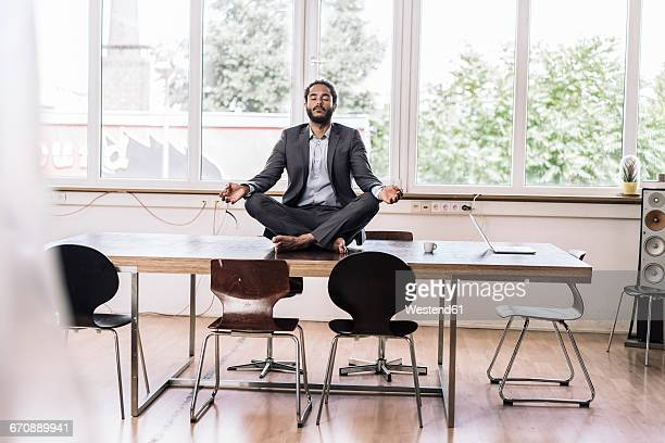 Young businessman sitting cross-legged on desk in office