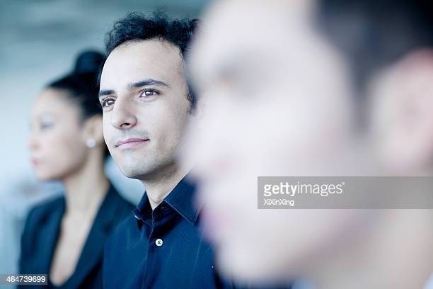 Young businessman sitting in a business meeting with colleagues