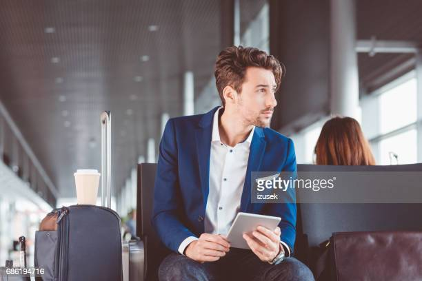Young businessman sitting in airport waiting area