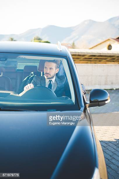 Young businessman sitting in car