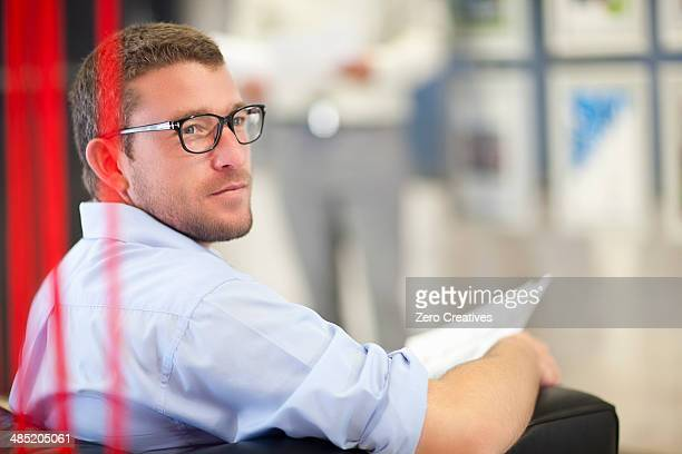 Young businessman sitting in office with paperwork