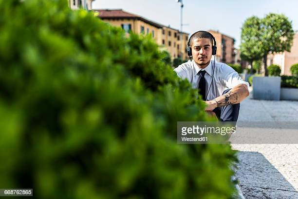 Young businessman sitting on a wall listening music with headphones