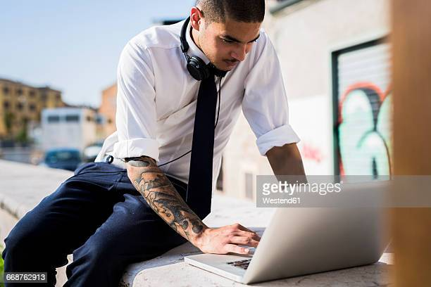 Young businessman sitting on a wall using laptop