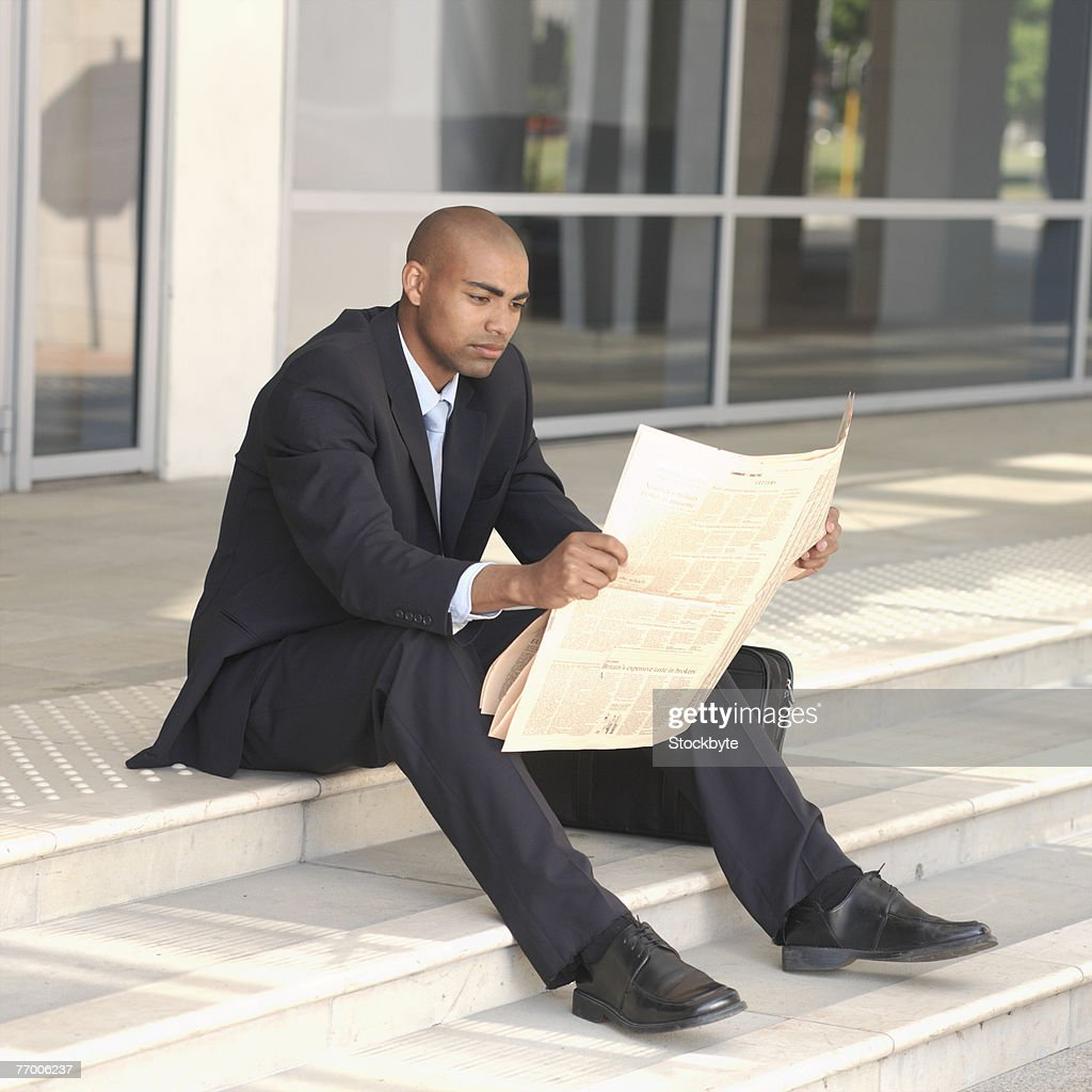 Young businessman sitting on steps outside building, reading newspaper : Stock Photo
