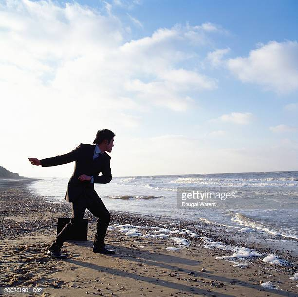 Young businessman skimming stones from beach, side view