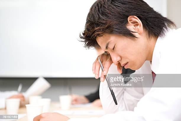 Young businessman sleeping during meeting