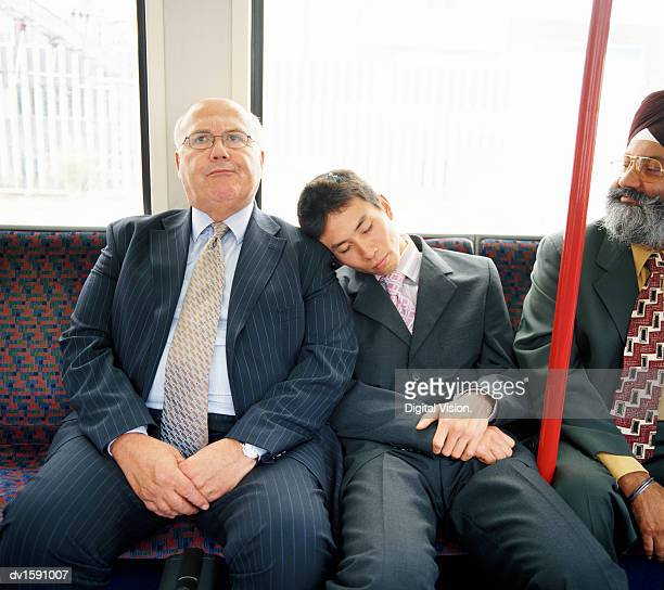 Young Businessman Sleeps on the Shoulder of a Mature Businesman on a Train