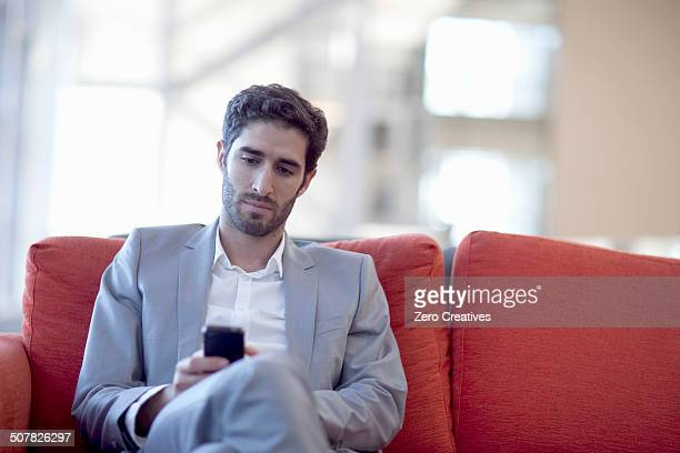 Young businessman smartphone texting on sofa in conference centre