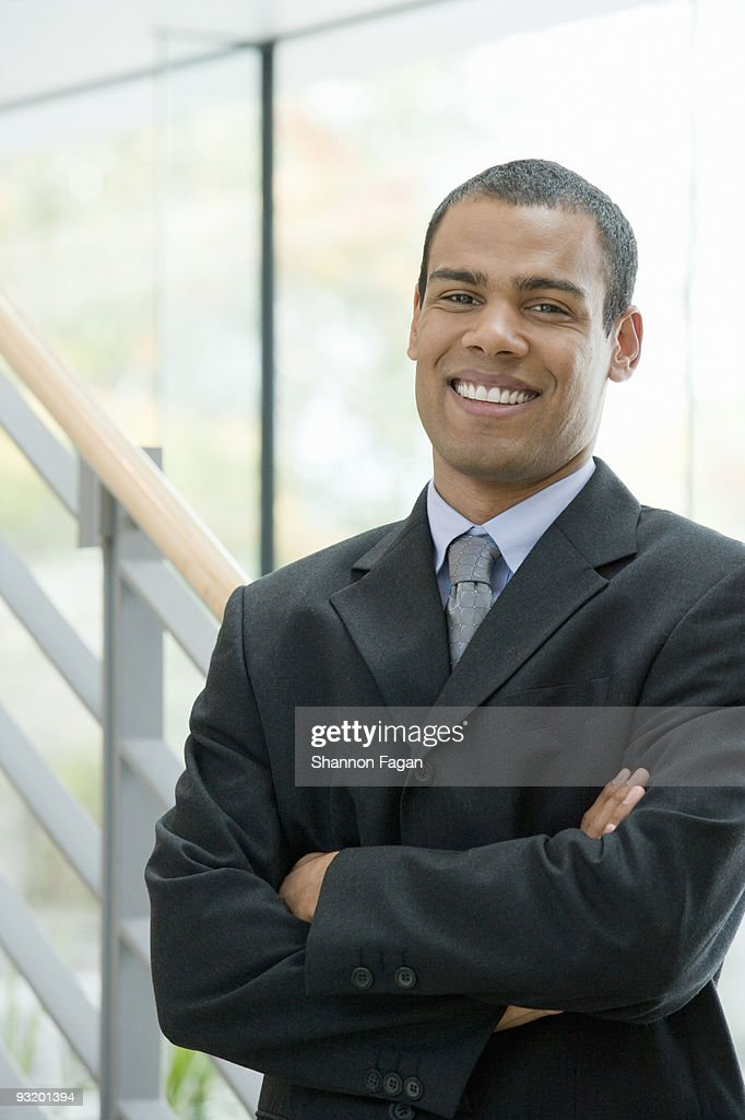 Young businessman smiling and crossing arms : Stock Photo