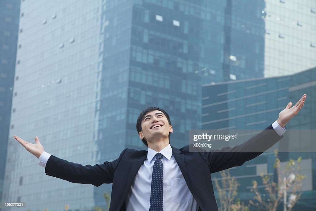 Young businessman smiling and standing outside with arms outstretched : Stock Photo