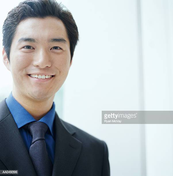 Young businessman smiling, close-up, portrait