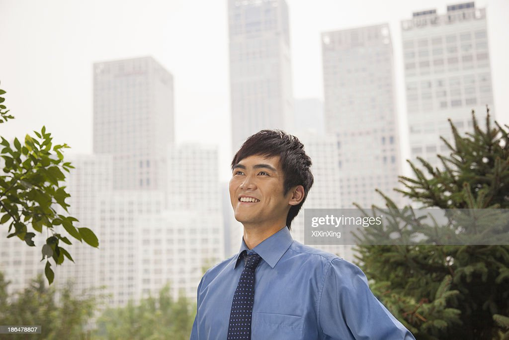 Young businessman smiling in the park, portrait : Stock Photo
