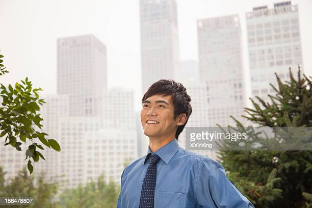 Young businessman smiling in the park, portrait