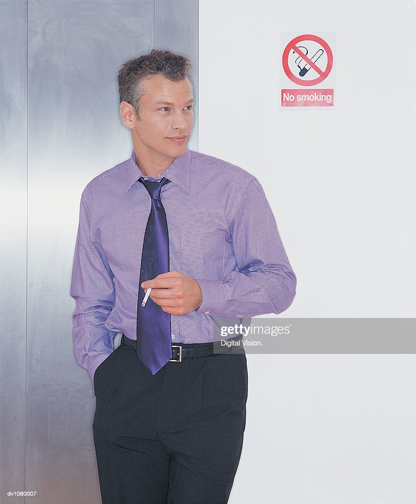 Young Businessman Smoking a Cigarette Next to a No Smoking Sign : Stock Photo