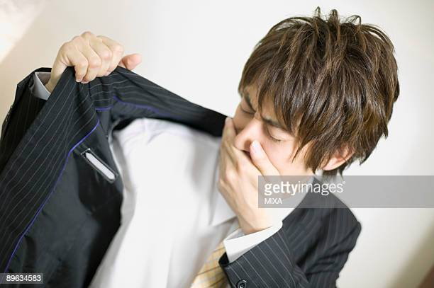 Young businessman sniffing his underarm