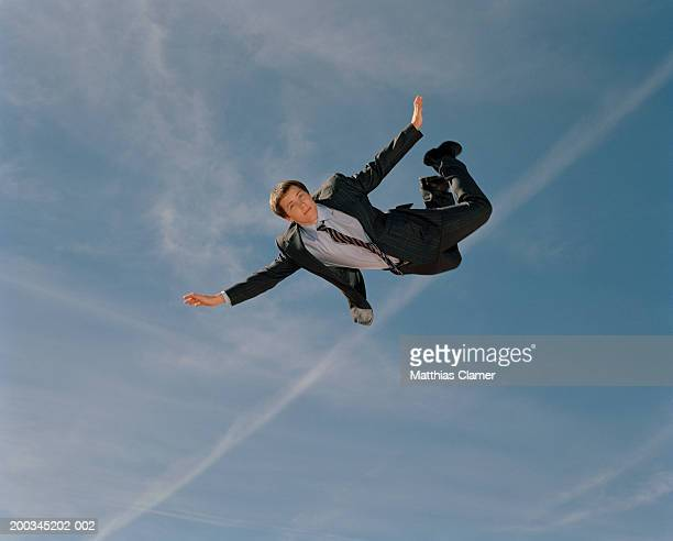 Young businessman soaring through sky, portrait, low angle view