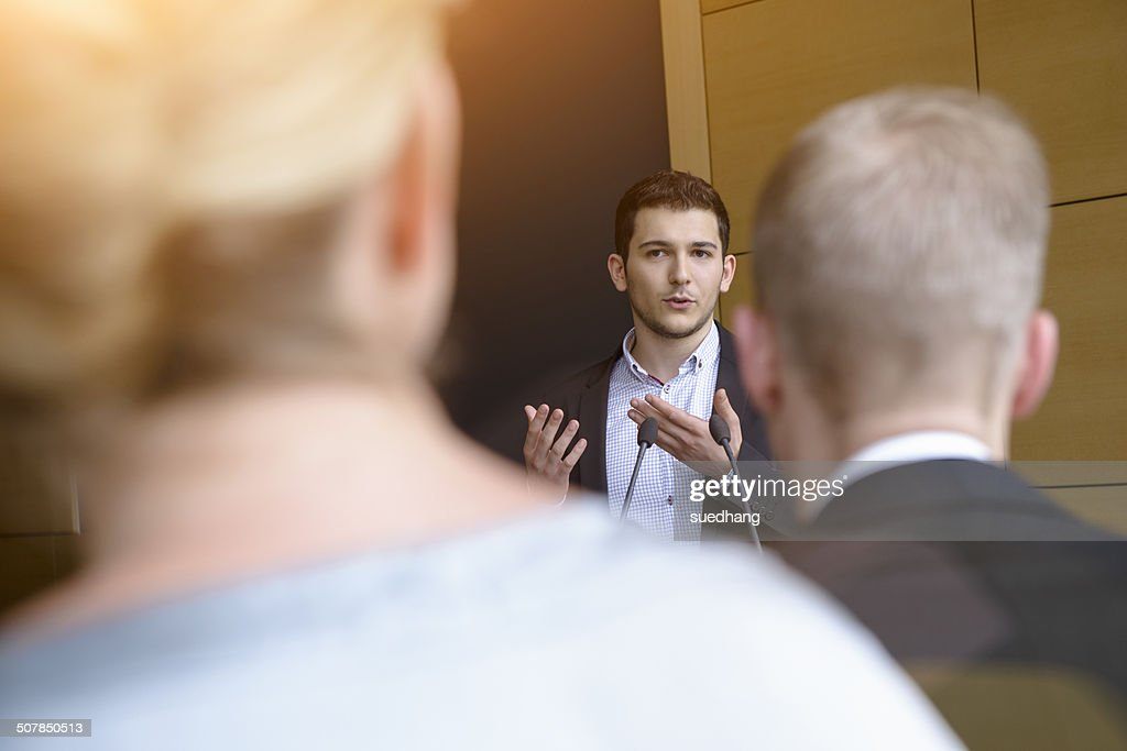 Young businessman speaking to audience in conference room