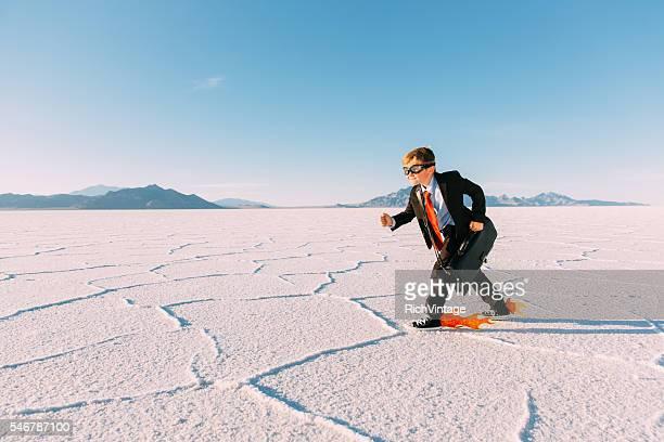 Young Businessman Speeds with Fire through Desert