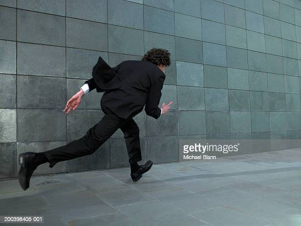 Young businessman sprinting along street, rear view