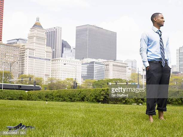 Young businessman standing barefoot in park